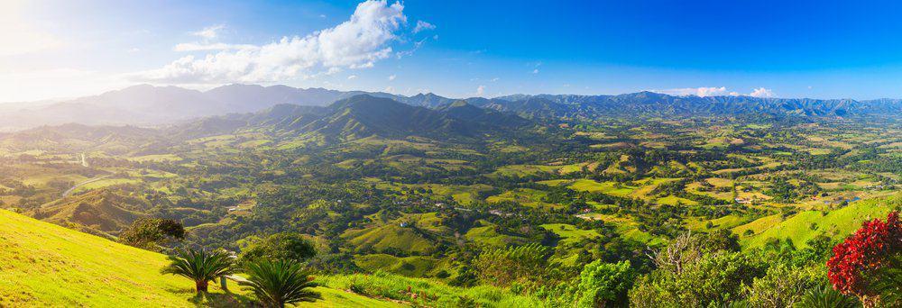 Un paisaje verde con montañas en la distancia y nubes blancas en un cielo azul.