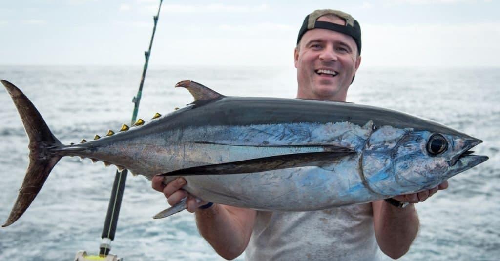 Happy angler holding big tuna fish